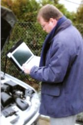 expert auto avec un outils informatiques portables qui enregistre les informations recueillies.